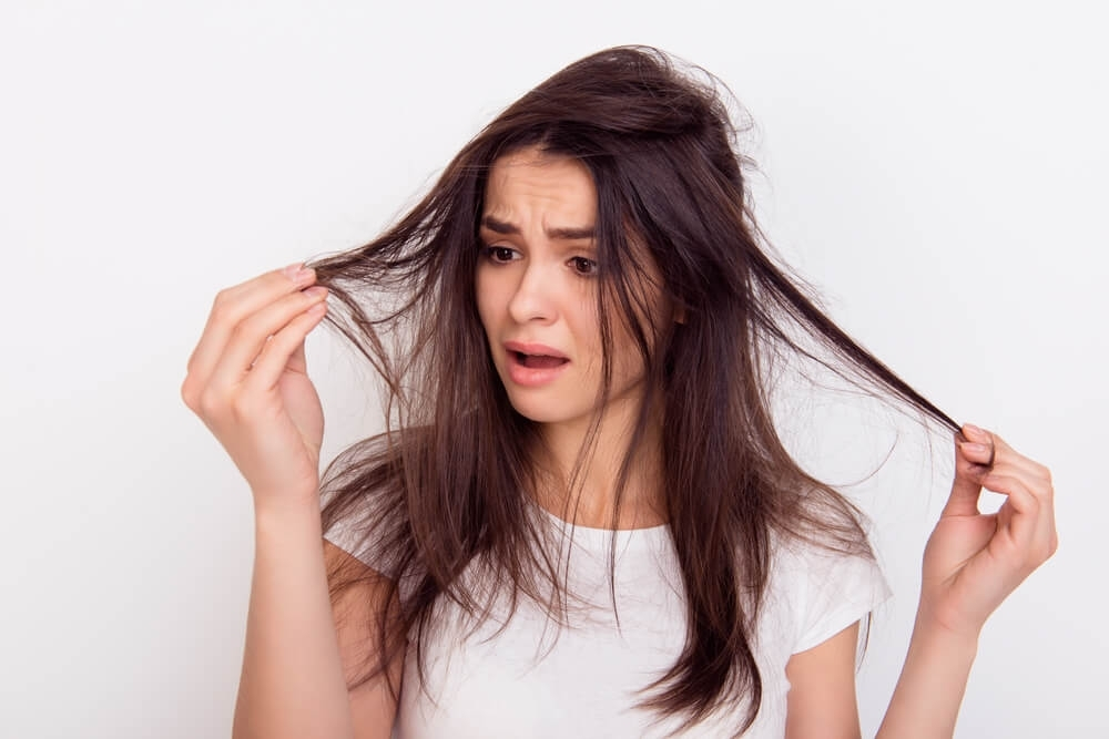 woman looking concerned at hair